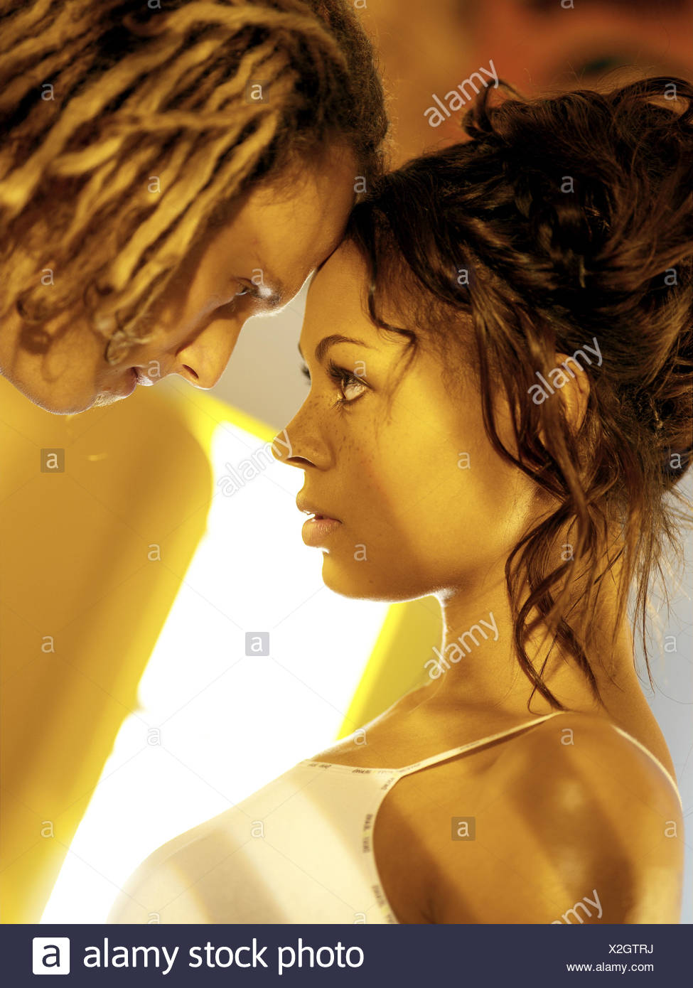 Couple, young, skin colour differently, falls in love, eye contact, page portrait at lovers, at lovers, ethnically merged, nationality different, woman swarthy, man, dreadlocks, Rasta hairstyle, love, partnership, respect, flirtation, affection, touch, suture, closely packed, look, intensely, passionately, feelings, emotion, desire, longing, desire, strength, page portrait, summery, background fridge, openly, heat, summer, inside, colour mood, colour yellow Stock Photo
