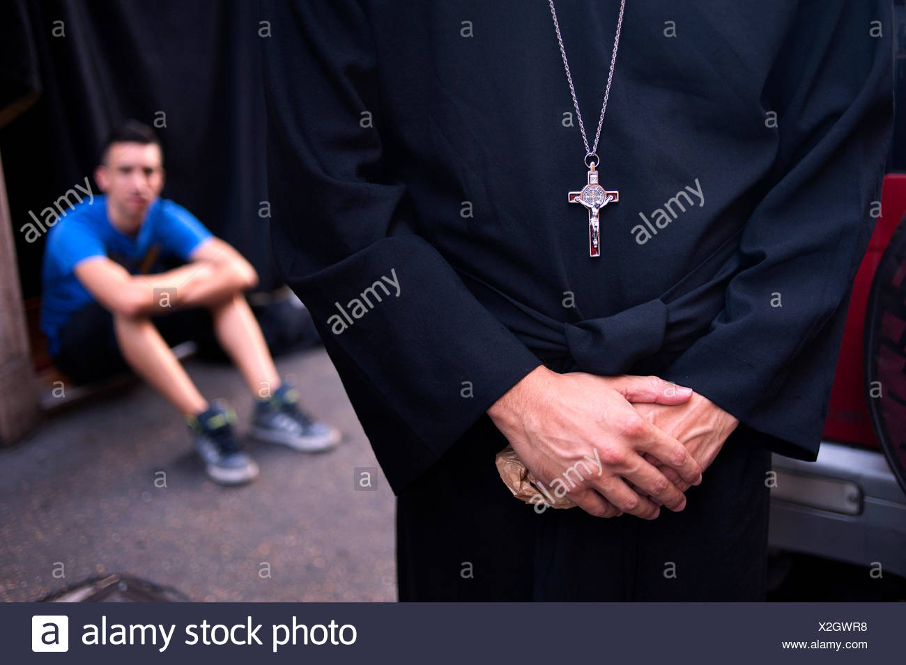 A priest folds his hands while a nearby man looks on. - Stock Image