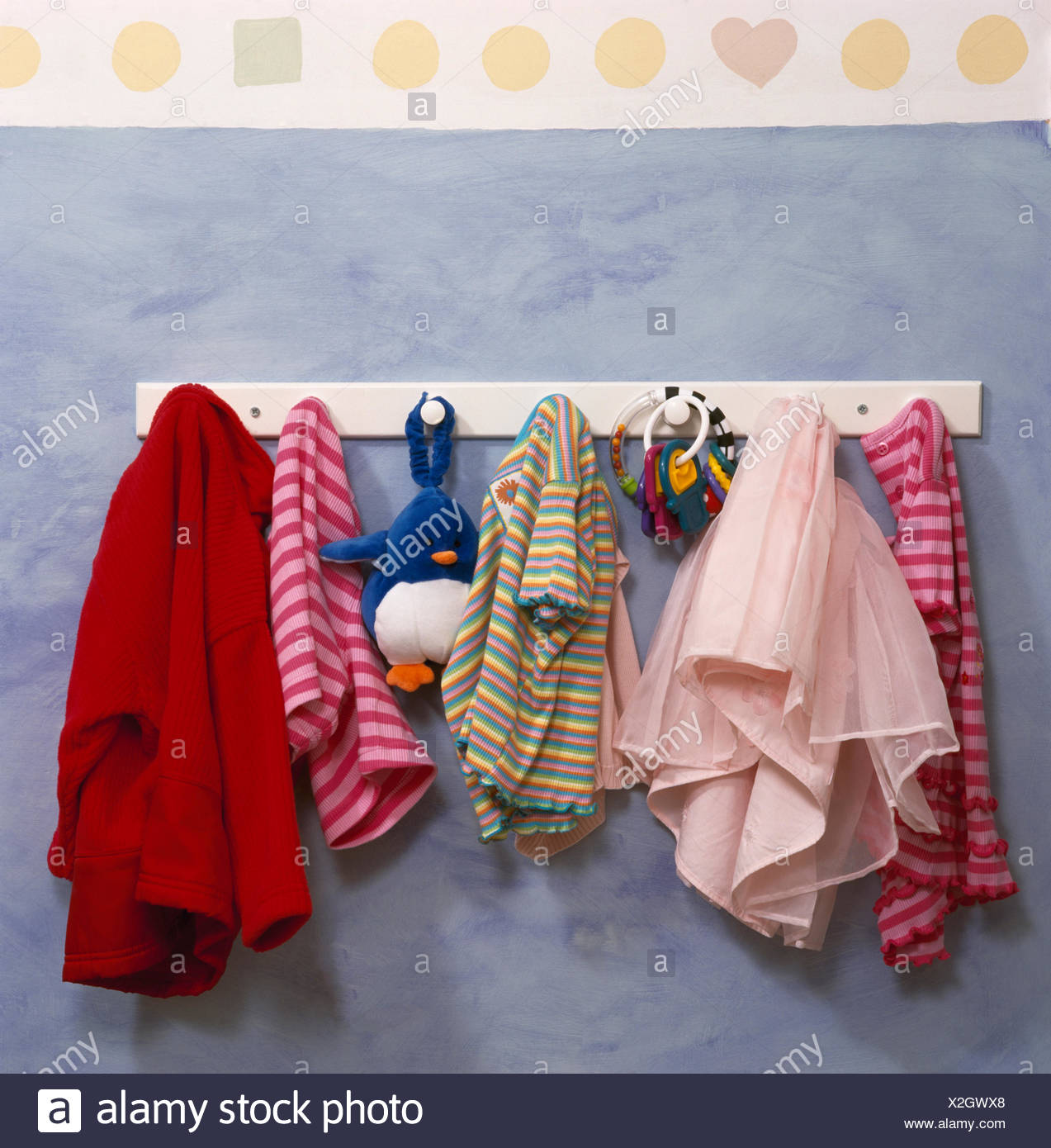 Close-up of children's clothes on a small peg rail - Stock Image