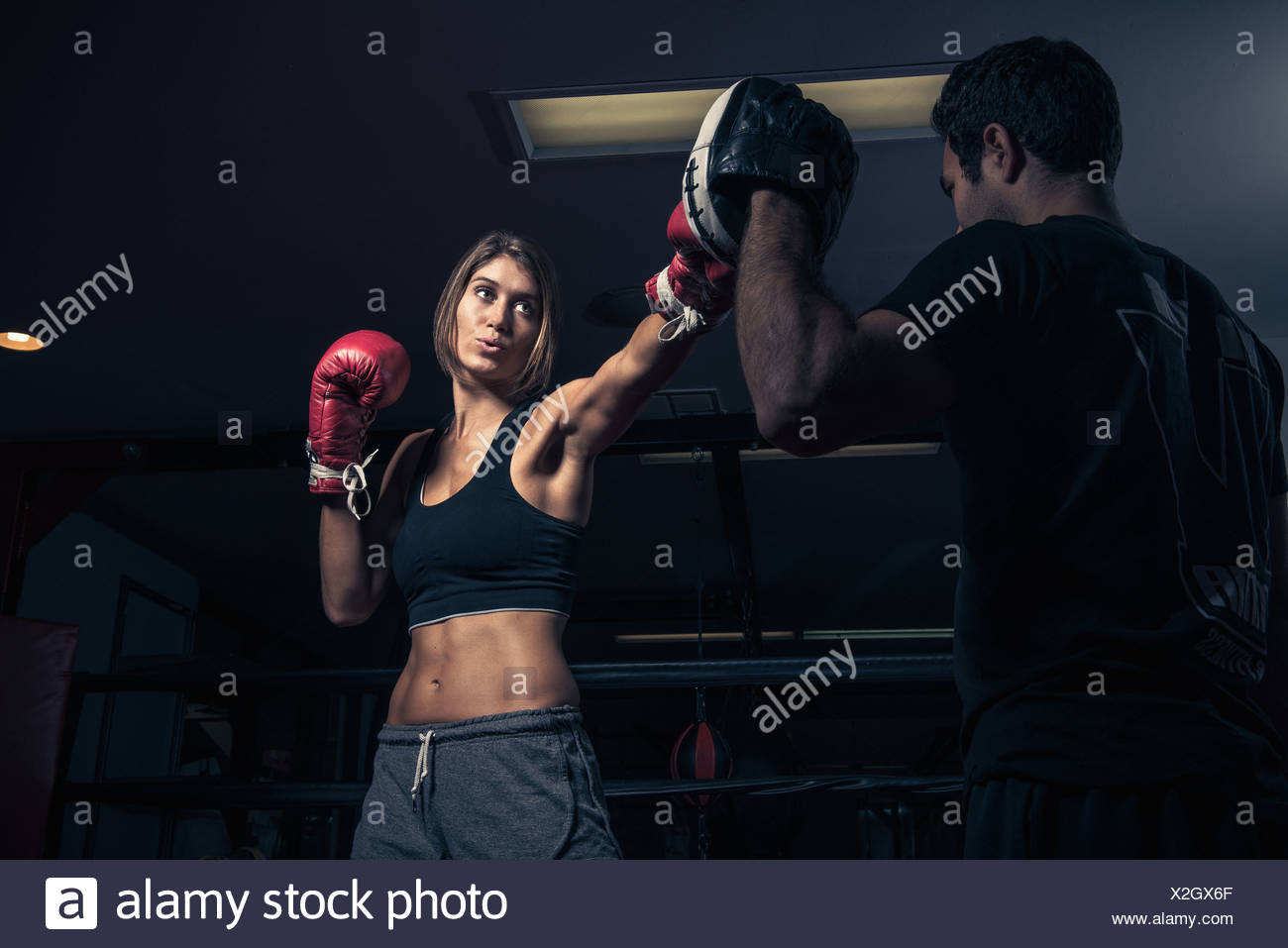 Female boxer punching instructor's punch shield - Stock Image