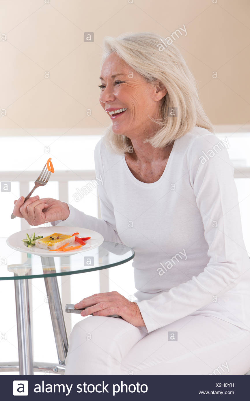 SENIOR EATING A MEAL - Stock Image