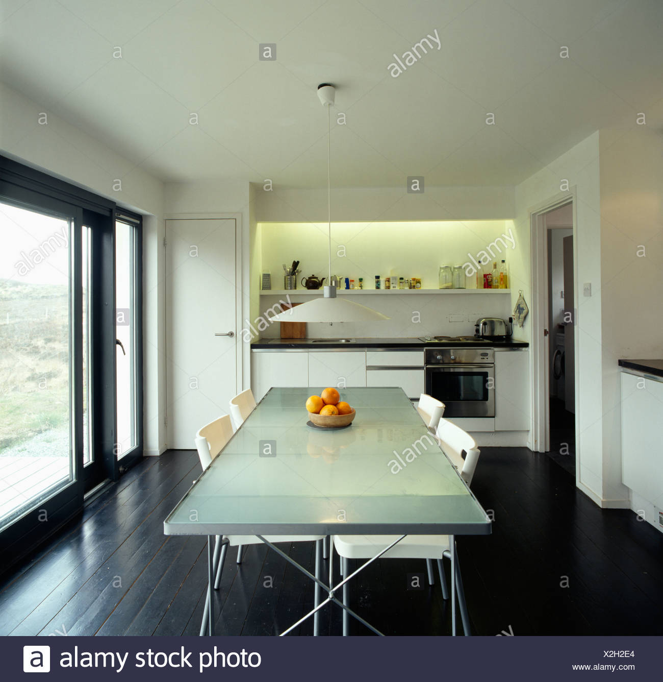 White Chairs At Opaque Glass Topped Table In Modern Kitchen Dining