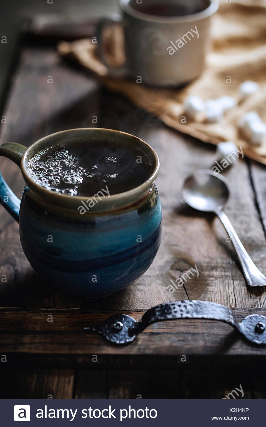 Handmade stone mug of steaming hot tea on rustic wood serving tray with morning light coming in behind. - Stock Image