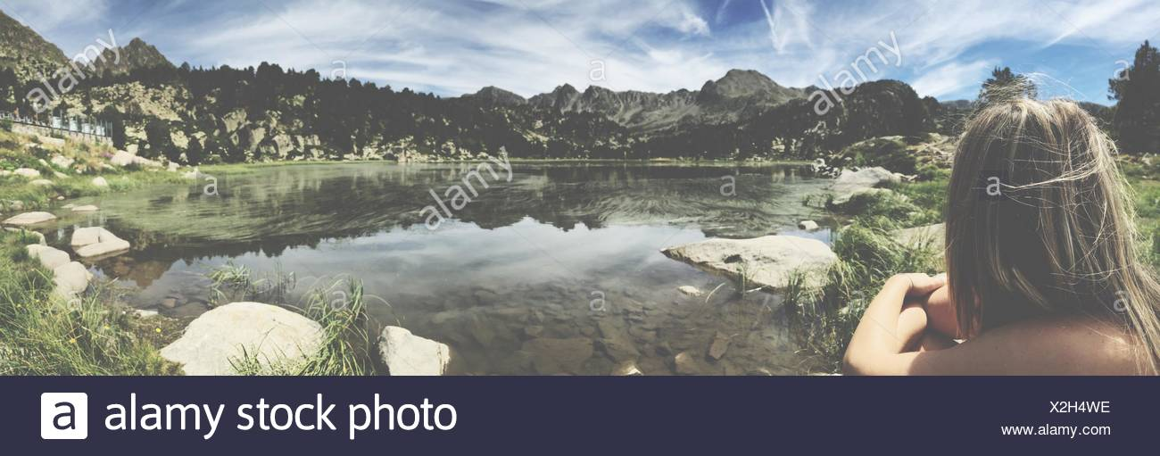 Rear View Of Woman Sitting On Lakeshore Against Cloudy Sky - Stock Image
