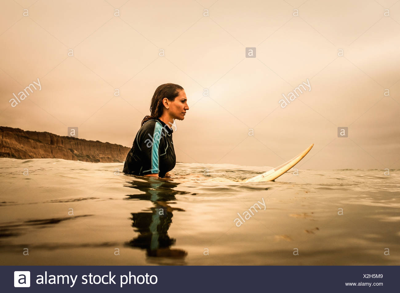 Young woman in sea with surfboard, profile - Stock Image