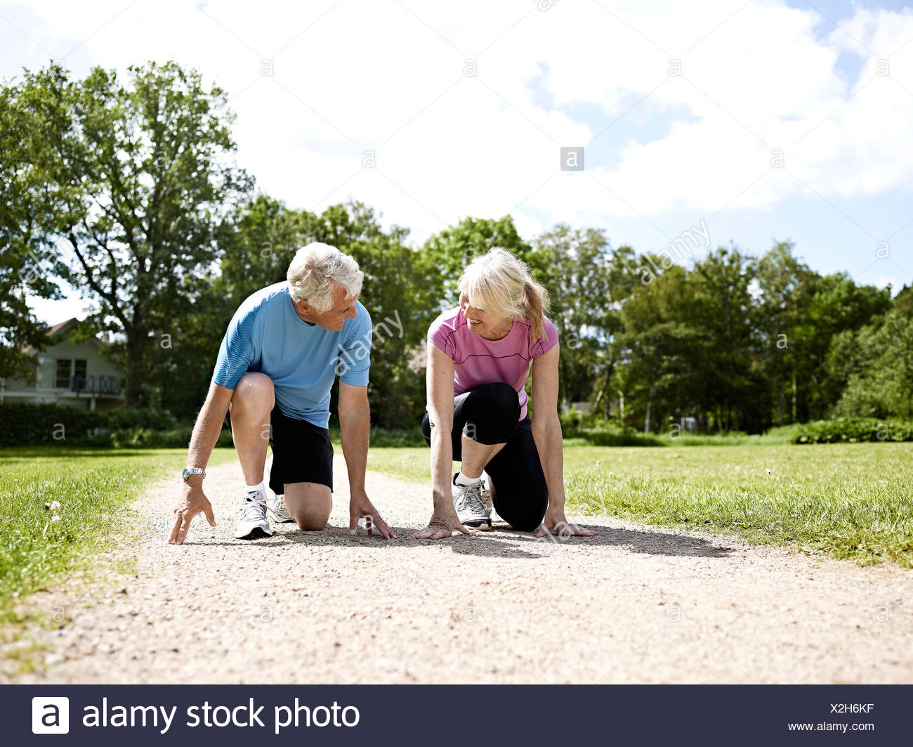 Older couple crouched in start position Stock Photo