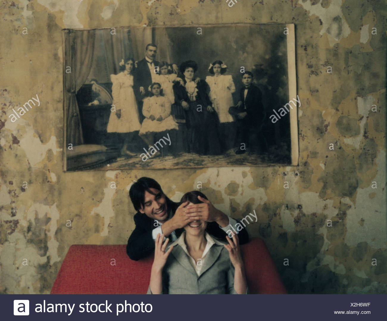 Man behind a woman sitting on red sofa, covering eyes, under black and white photo on wall - Stock Image