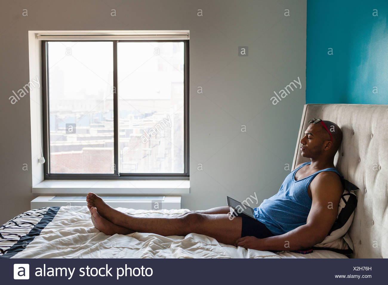 Mid adult man sleeping in bedroom - Stock Image