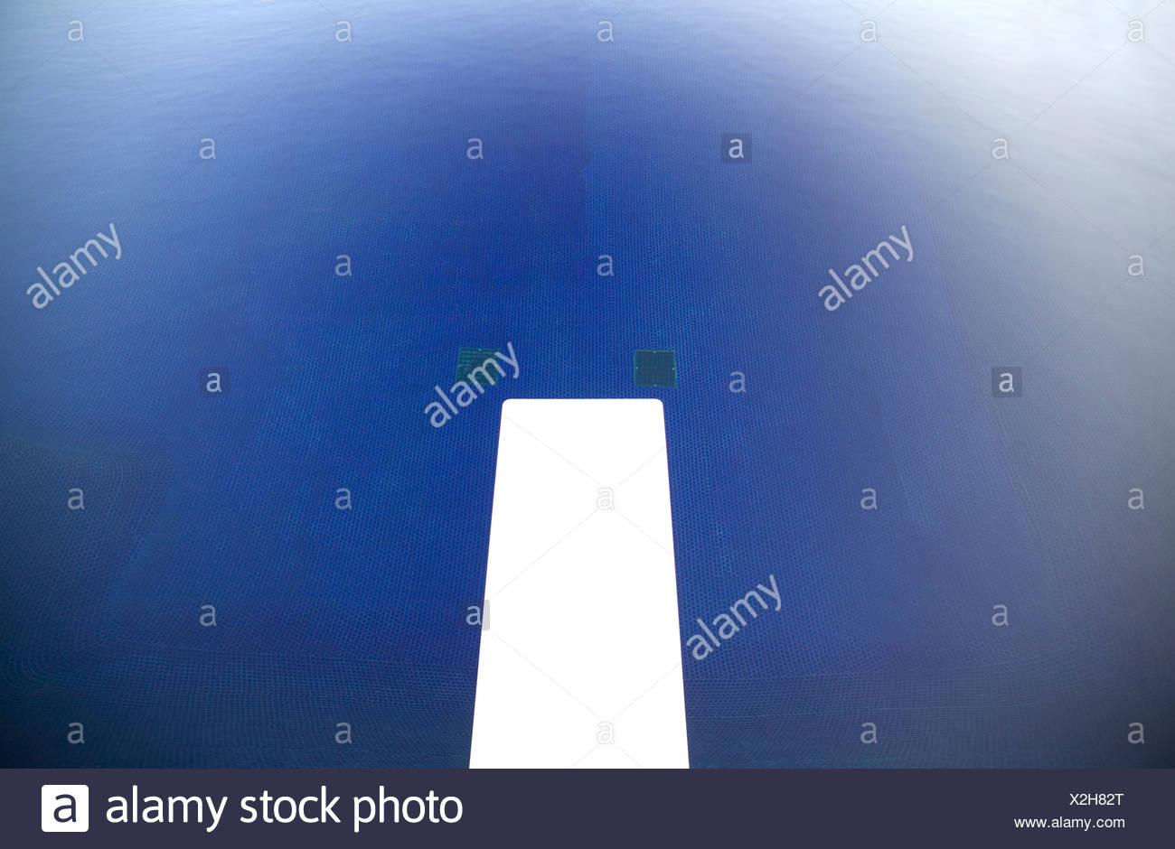 A white diving board above a blue pool, Folsom, California. - Stock Image
