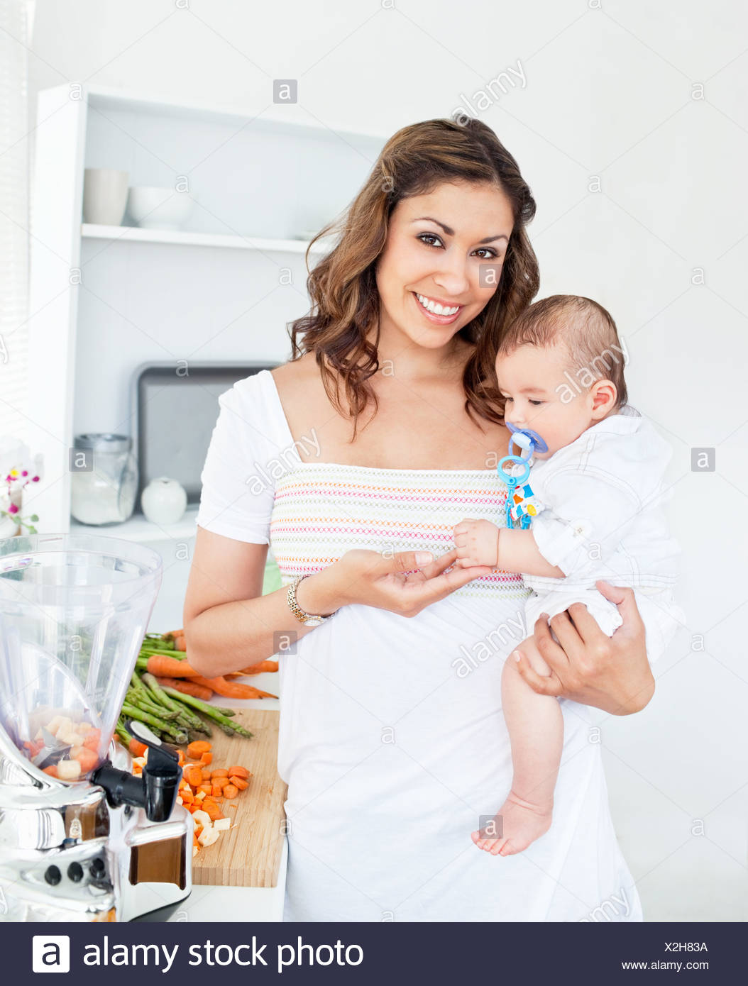 Portrait of a radiant mother holding her baby after preparing the lunch - Stock Image