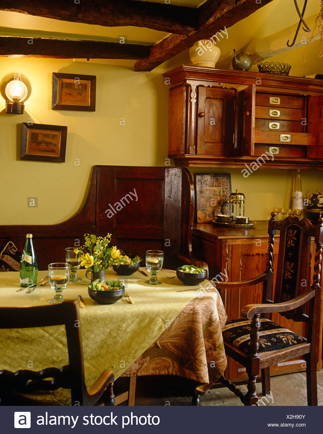 Jacobean style chairs at table with yellow cloth set for lunch in country dining room with old wooden cupboards Stock Photo