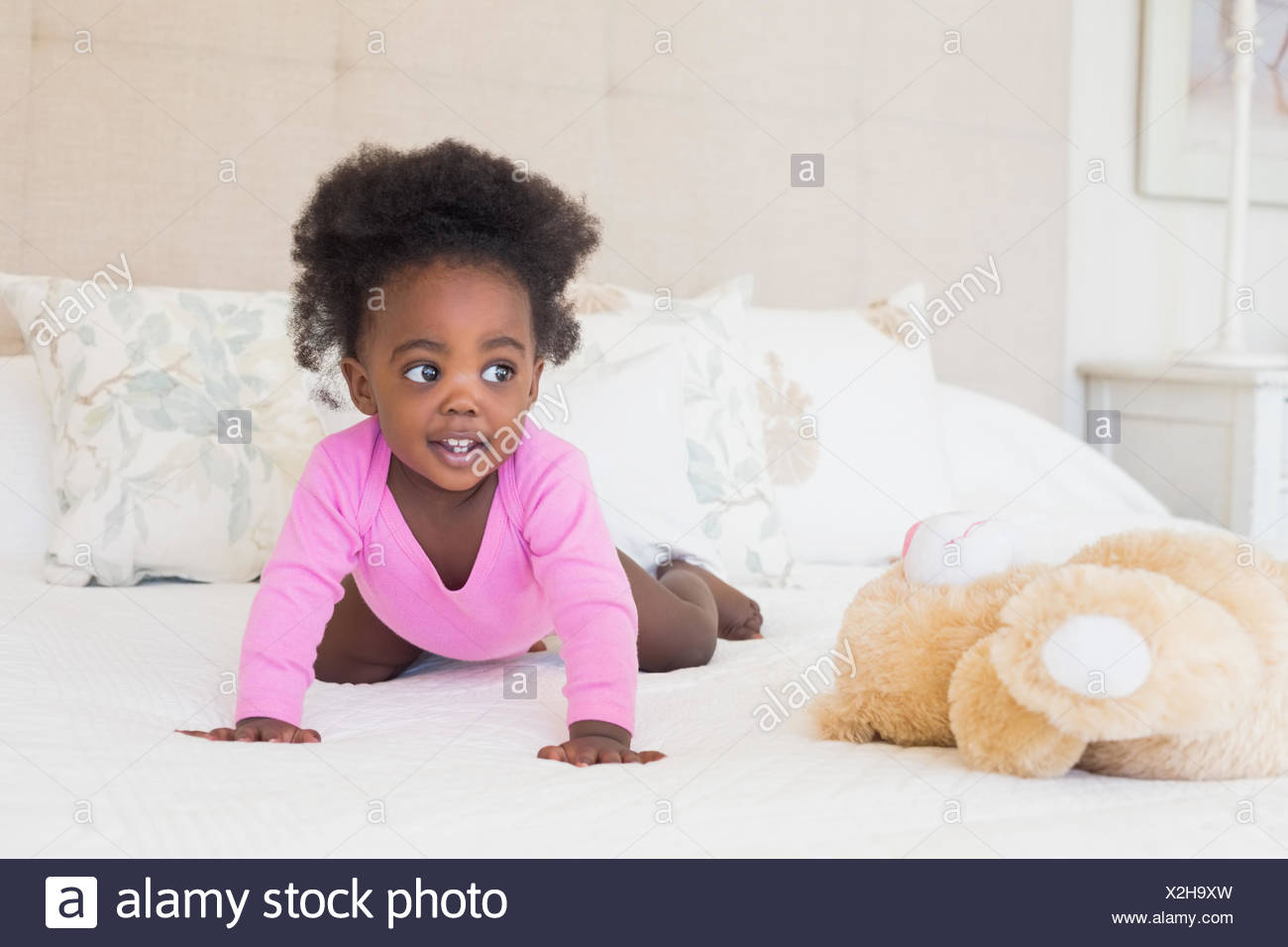 Baby girl in pink babygro crawling on bed - Stock Image