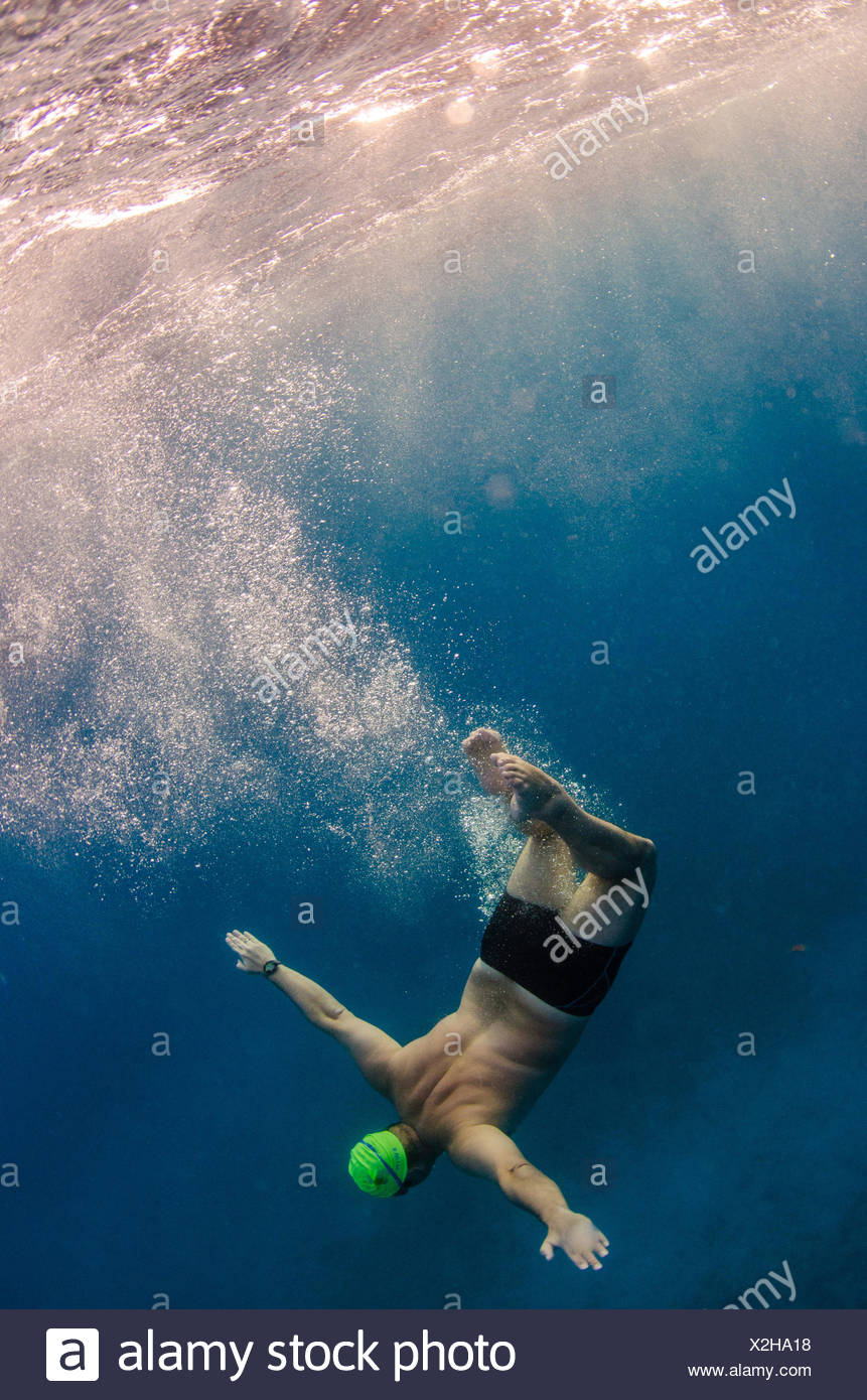 A man in a green swim cap and black bathing suit splashes and rolls underwater. - Stock Image