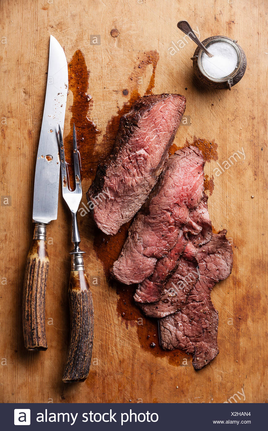 Roast beef with knife and fork for meat on wooden background - Stock Image