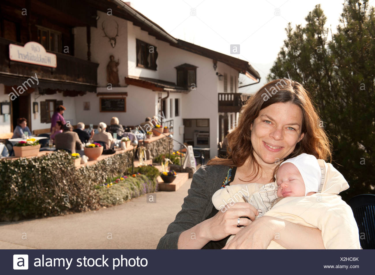 Smiling mother with sleeping newborn baby in her arms, dressed warm, terrace of the restaurant Cafe Winklstueberl, Fischbachau - Stock Image