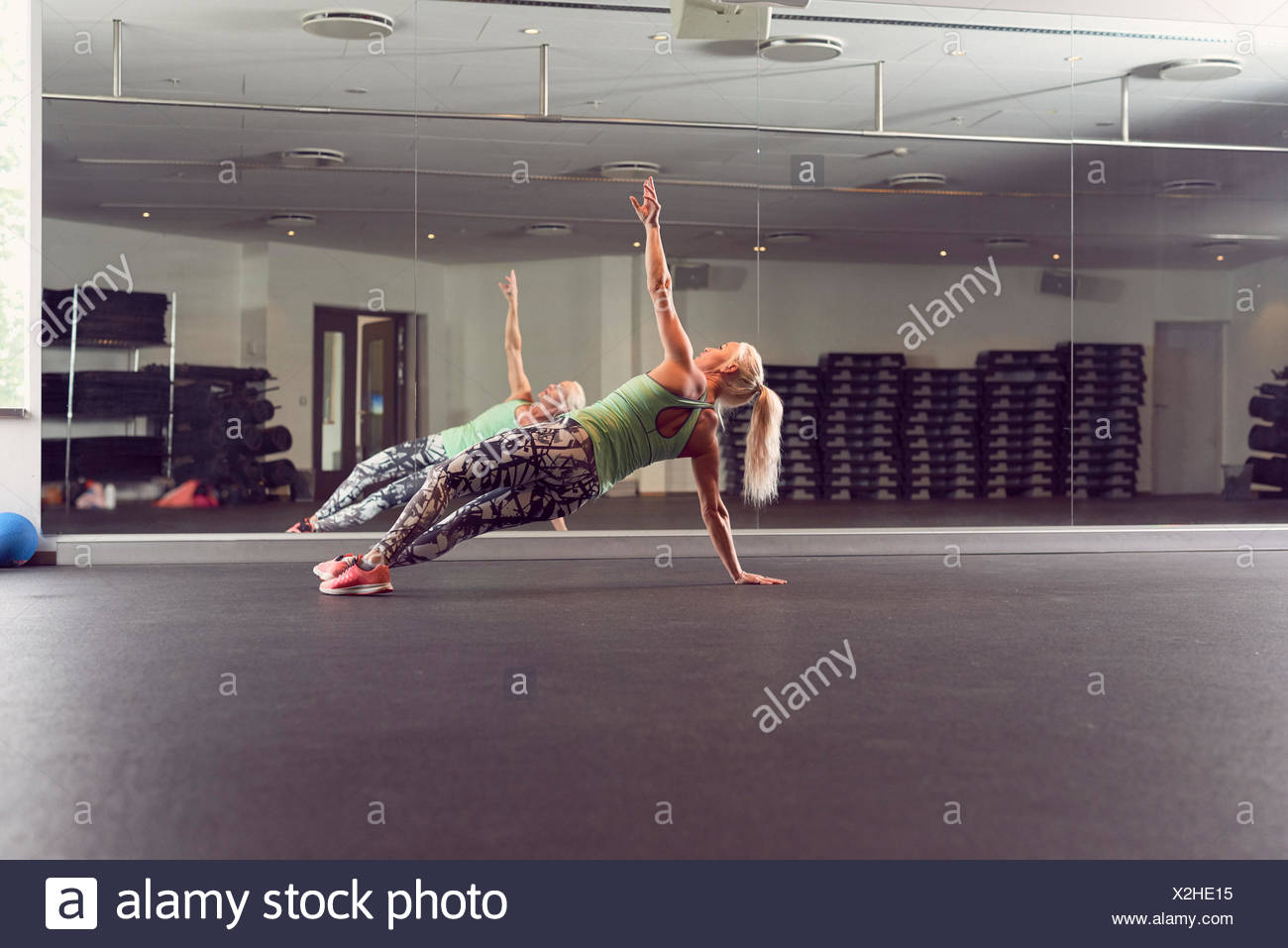 Woman doing side plank in gym - Stock Image