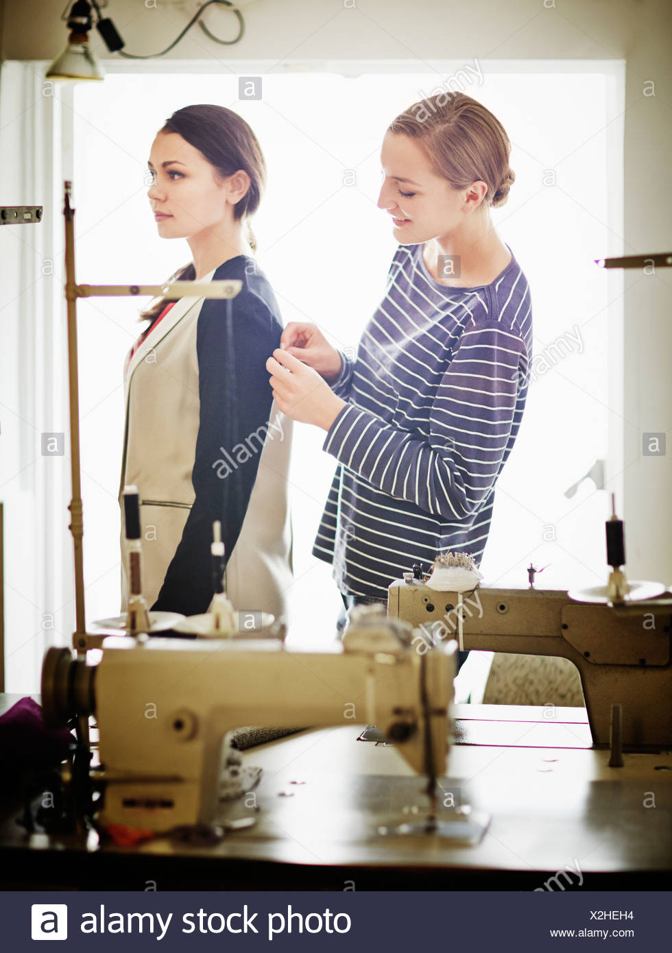 Seamstress adjusting woman's jacket - Stock Image
