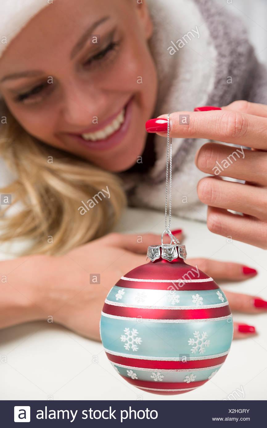 Frau mit Weihnachtsmütze hält schaut sich eine Christbaumkugel an die an ihrem Finger baumelt und denkt schon freudig an Weihnachten. Die Fingernägel sind schon auf Weihnachten abgestimmt. - Stock Image