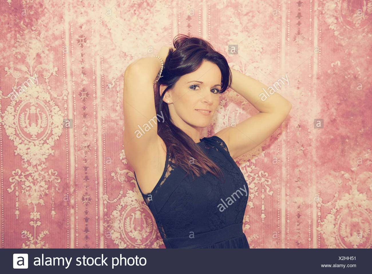 Woman with her hands behind her head - Stock Image