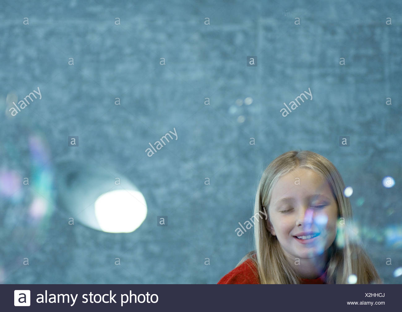 Girl closing eyes as bubbles float in the air Stock Photo