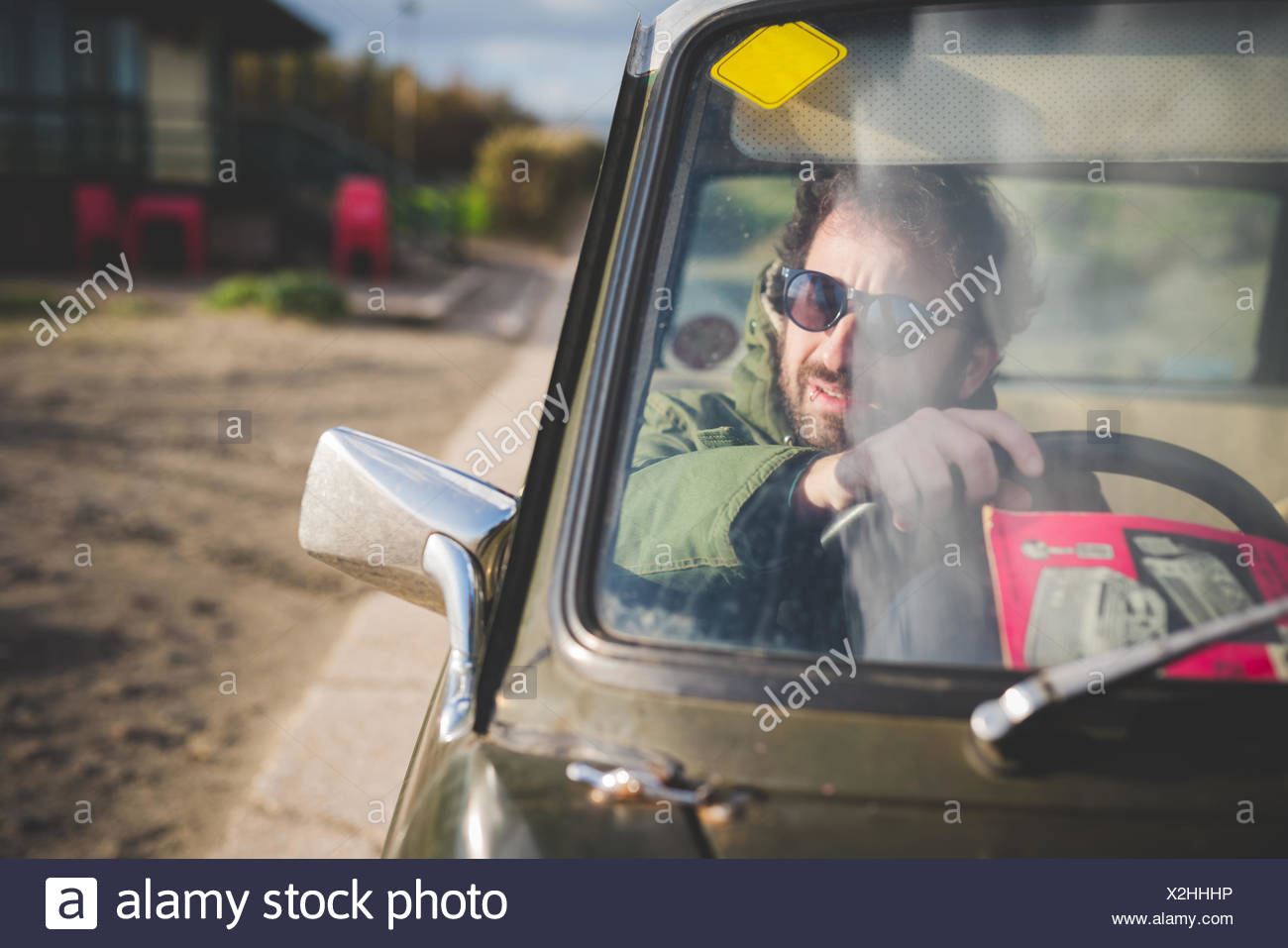 Man in parked vintage car looking through wing mirror - Stock Image