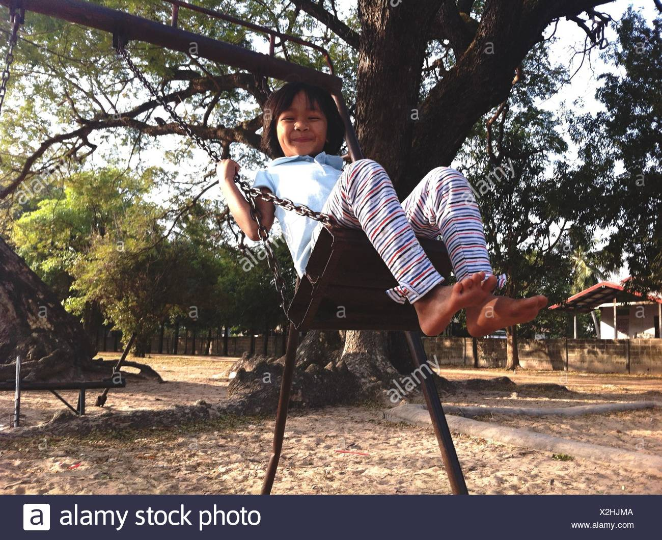 Girl Swinging On Chain Swing Ride And Smiling - Stock Image