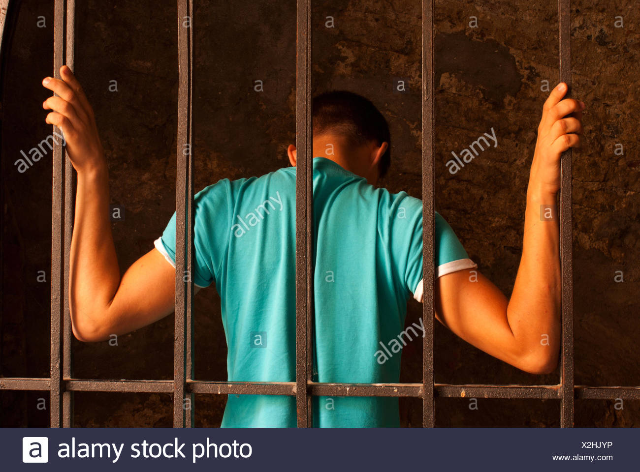 Man with hands tied with rope behind the bars - Stock Image