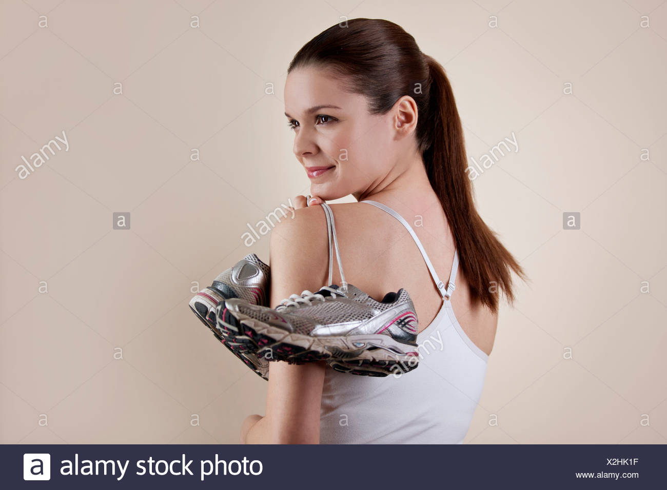 A young woman holding a pair of training shoes over her shoulder Stock Photo