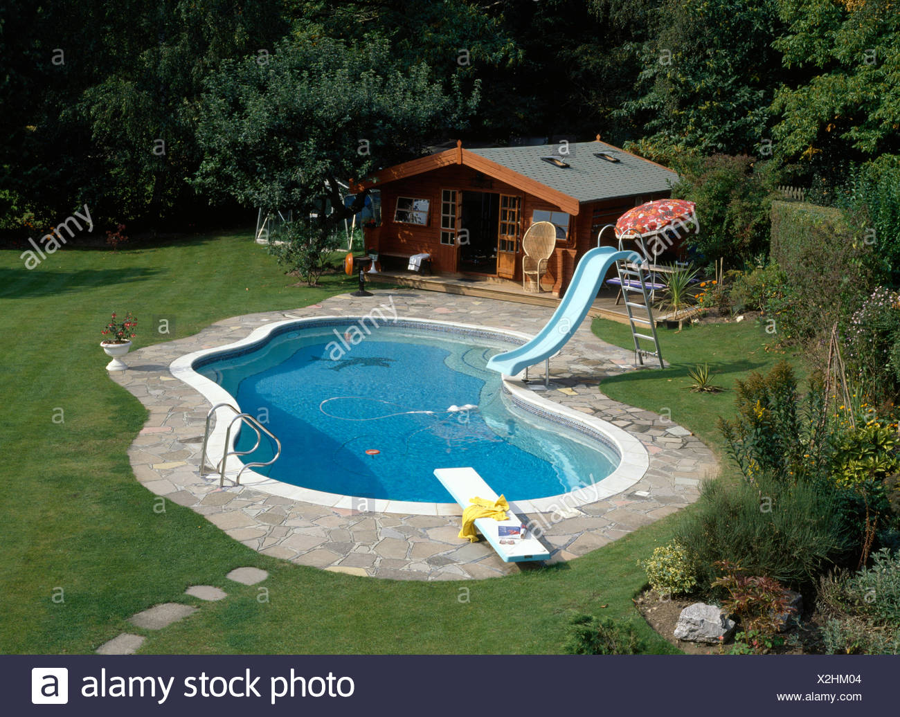 Birds-eye view of a kidney shaped swimming pool with a slide in ...