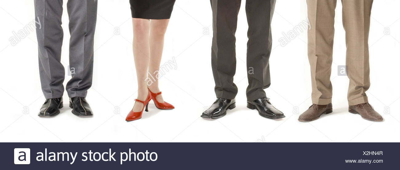 Three businessmen and a woman standing in a row, detail of legs - Stock Image