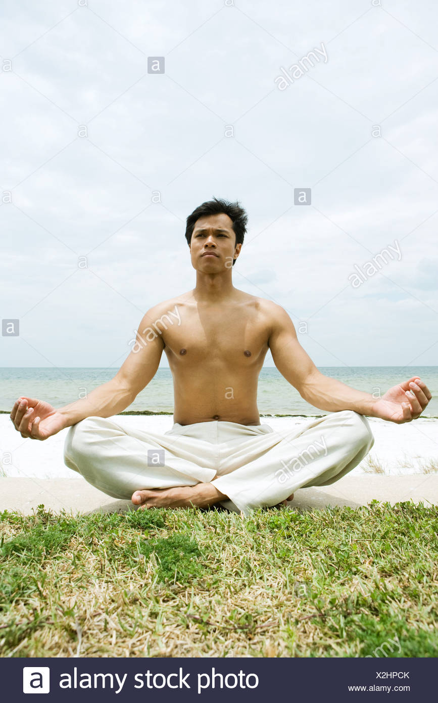 Barechested man sitting in lotus position, ocean in background, full length - Stock Image