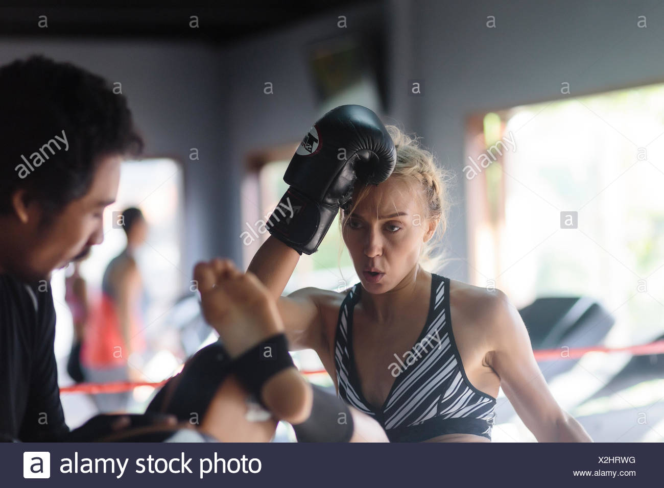 Young woman kicking while practicing kickboxing with coach, Seminyak, Bali, Indonesia - Stock Image
