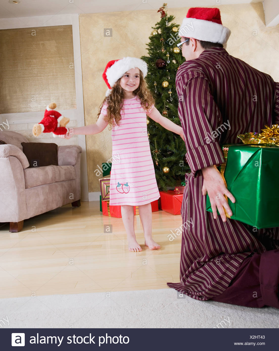 Girl (5-6) looking at father in Santa hat hiding present behind back - Stock Image