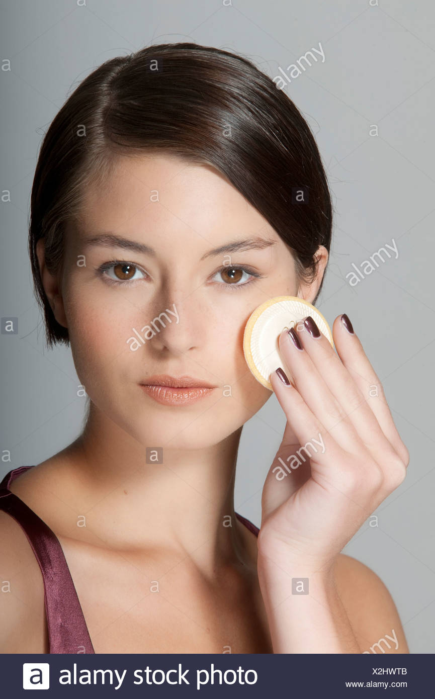 Step By Step Make Up Female Short Brunette Hair Applying Foundation To Her Cheek A Sponge Unsmiling Looking At Camera Stock Photo Alamy