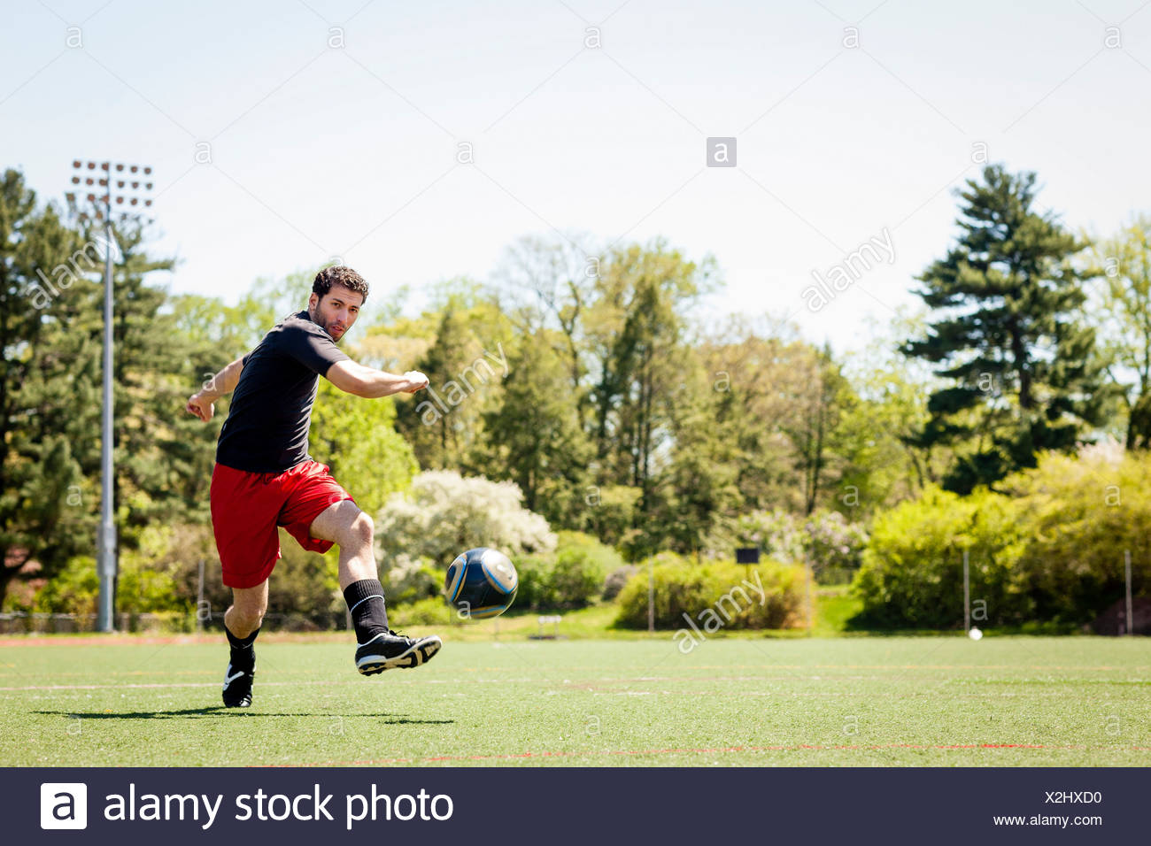 Soccer player running and kicking ball - Stock Image
