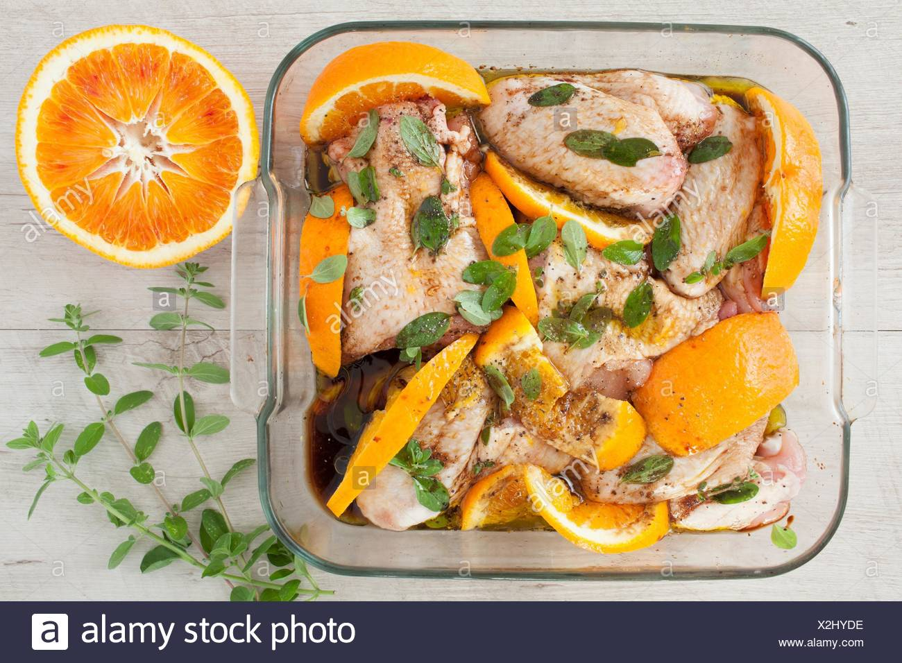 Top view of cooking pan with raw chicken wings marjoram, orange and soya sauce. - Stock Image