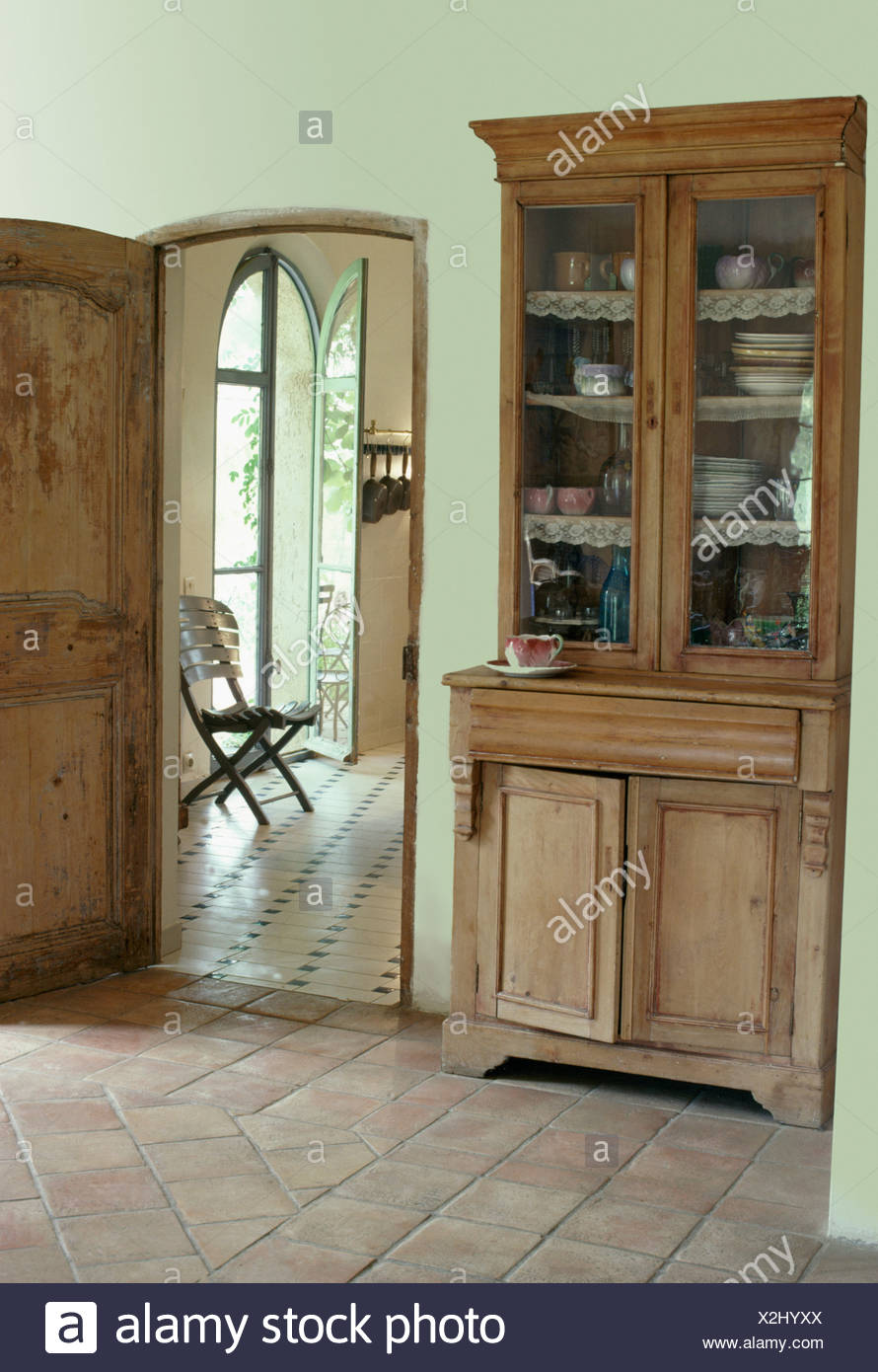Antique glass front dresser in french country hall with terracotta antique glass front dresser in french country hall with terracotta floor tiles dailygadgetfo Choice Image