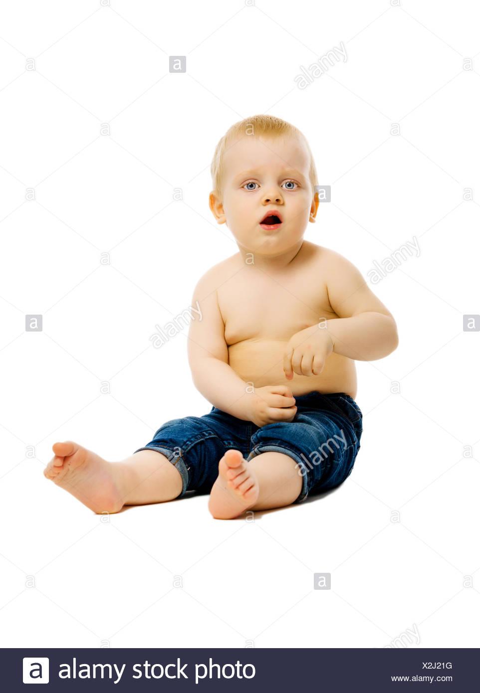 baby sitting on the floor. Studio. isolated - Stock Image