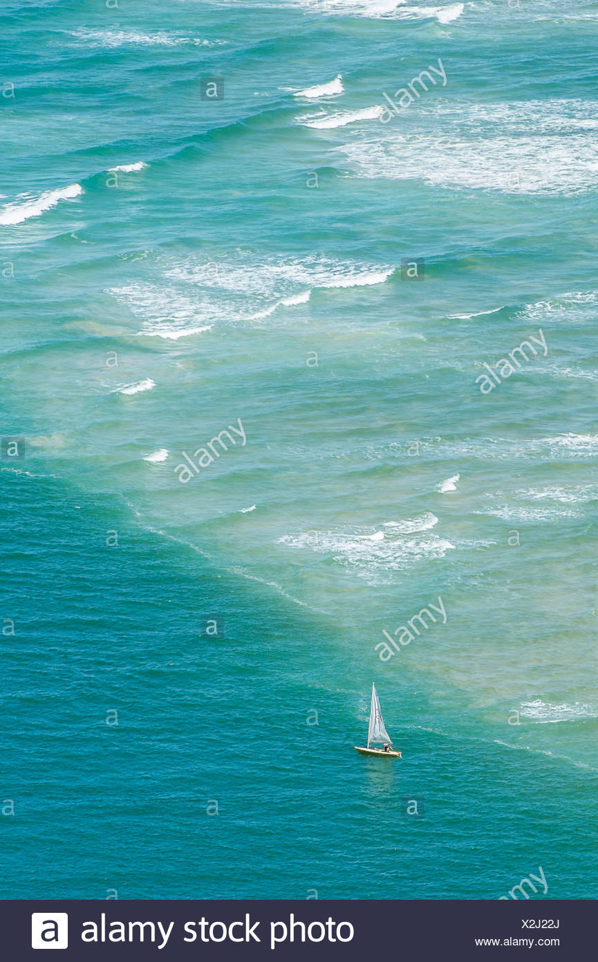 Sailboat cruising over small waves in the ocean - Stock Image