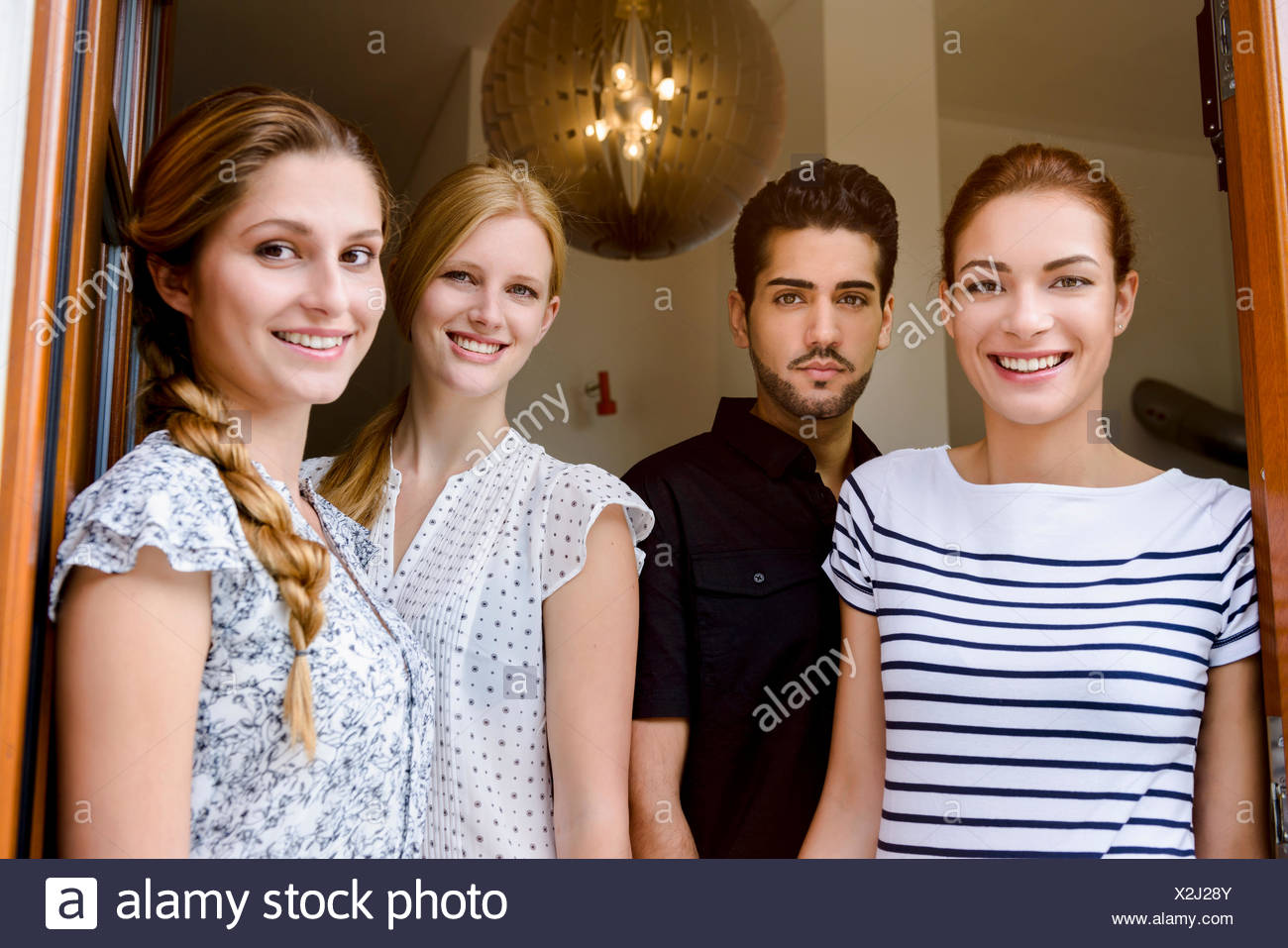 Four people looking at camera, portrait - Stock Image
