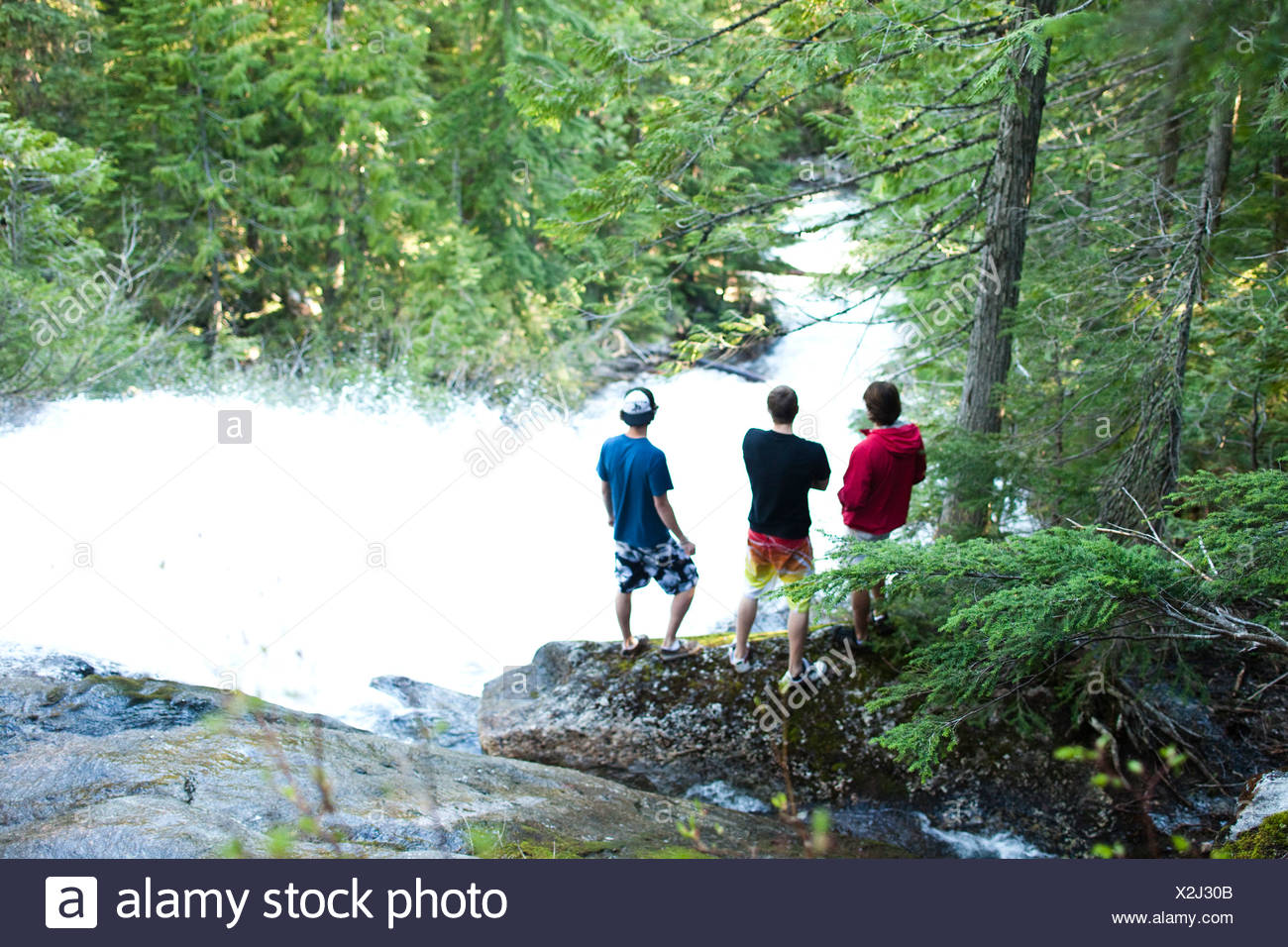 Three young men stand at the top of a large waterfall while hiking in the forests of Idaho. - Stock Image