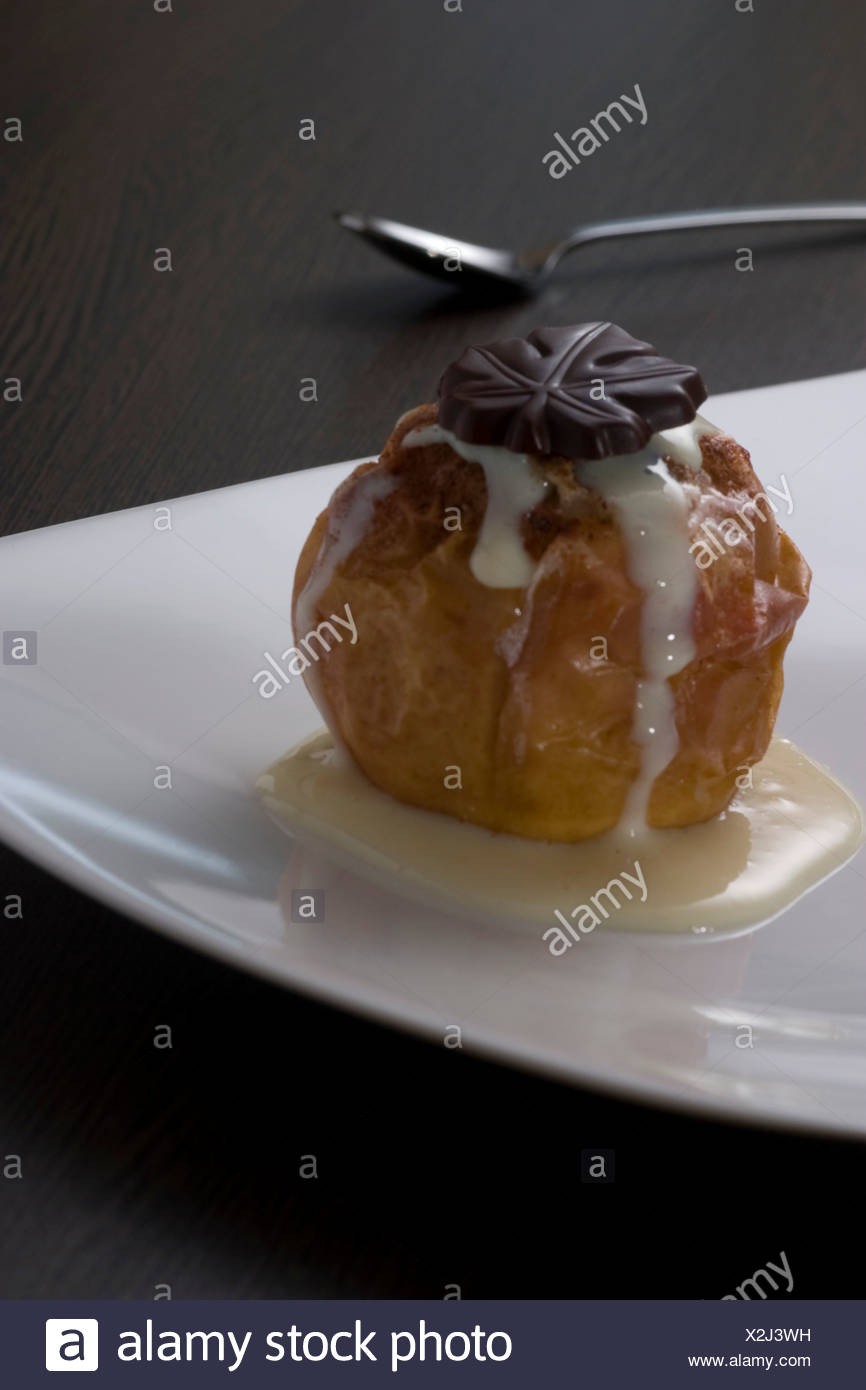 Baked apple filled with marzipan, dusted with cinnamon and covered in vanilla sauce on a plate - Stock Image