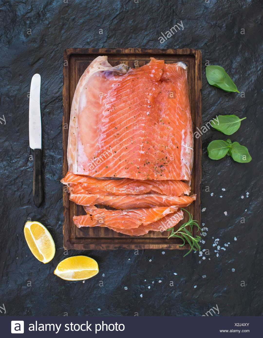 Smoked salmon filet with lemon, fresh herbs and bred on wooden serving board over dark stone backdrop, top view - Stock Image