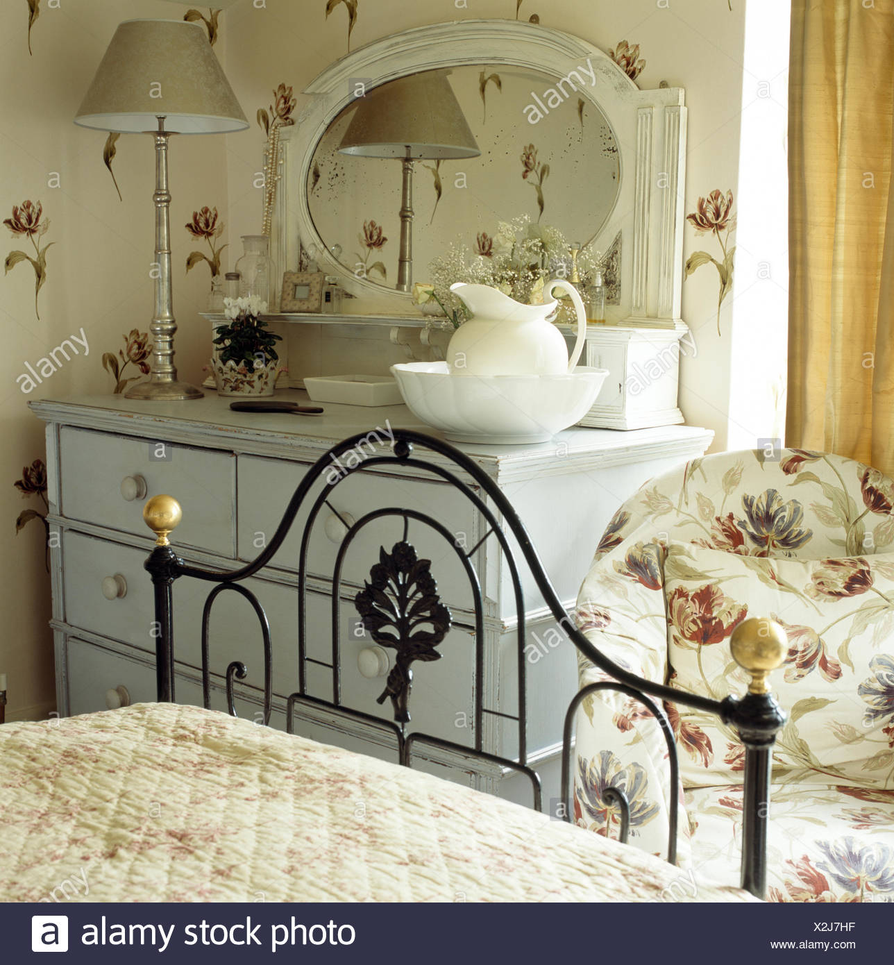 Picture of: Ornate Black Wrought Iron Bed In Cottage Bedroom With Tulip Patterned Chair And Painted Chest Of Drawers Stock Photo Alamy