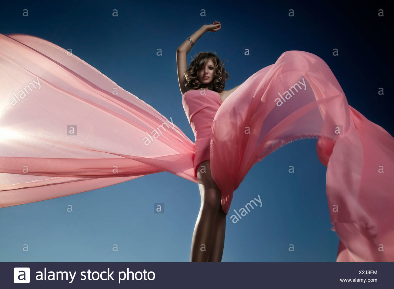 Young woman in a pink dress enveloped in billowing fabric, the setting sun behind her - Stock Image