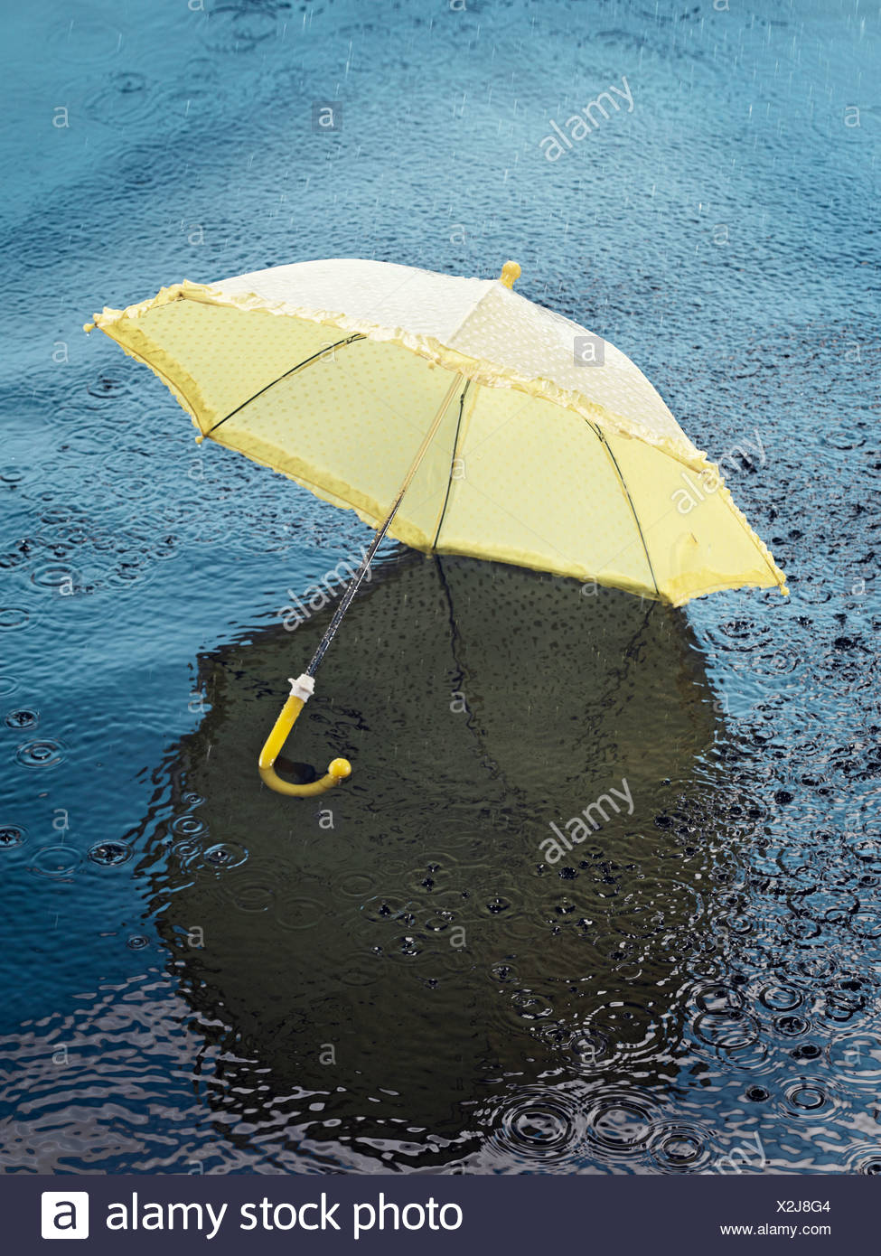 Umbrella floating on water, high angle view - Stock Image