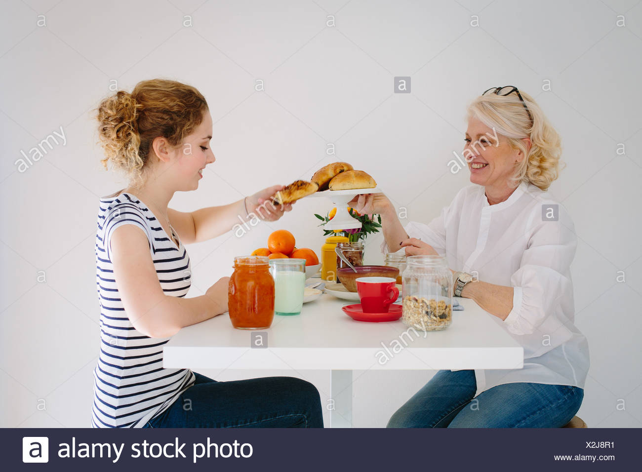 Mother and teenage daughter sharing breakfast - Stock Image