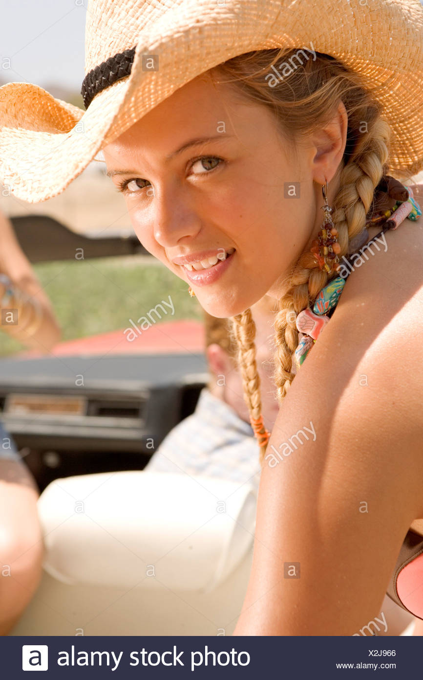 Young woman in cowboy hat smiling - Stock Image