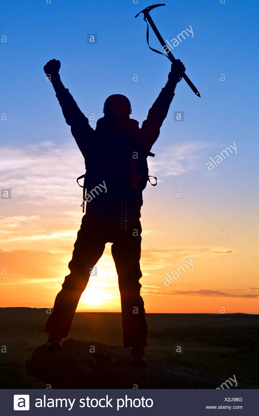 Silhouette climber on mountain top - Stock Image
