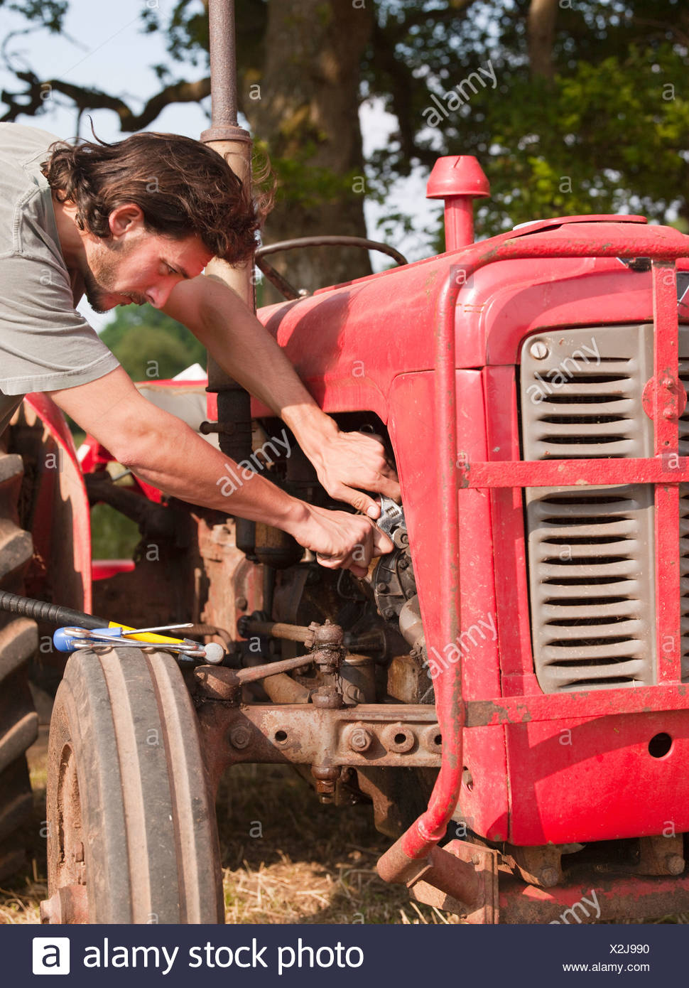 man using tools on tractor - Stock Image